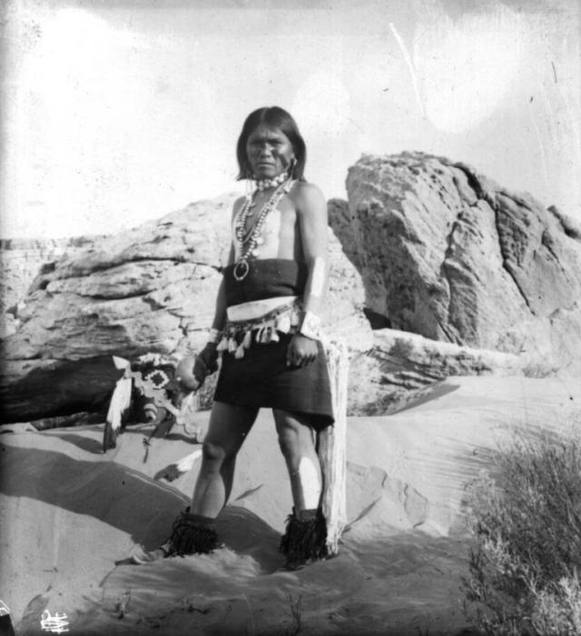 Muž z Antilopího bratrstva v tanečním úboru s náhrdelníky a chřestidly. Walpi, USA, Arizona, 1900.