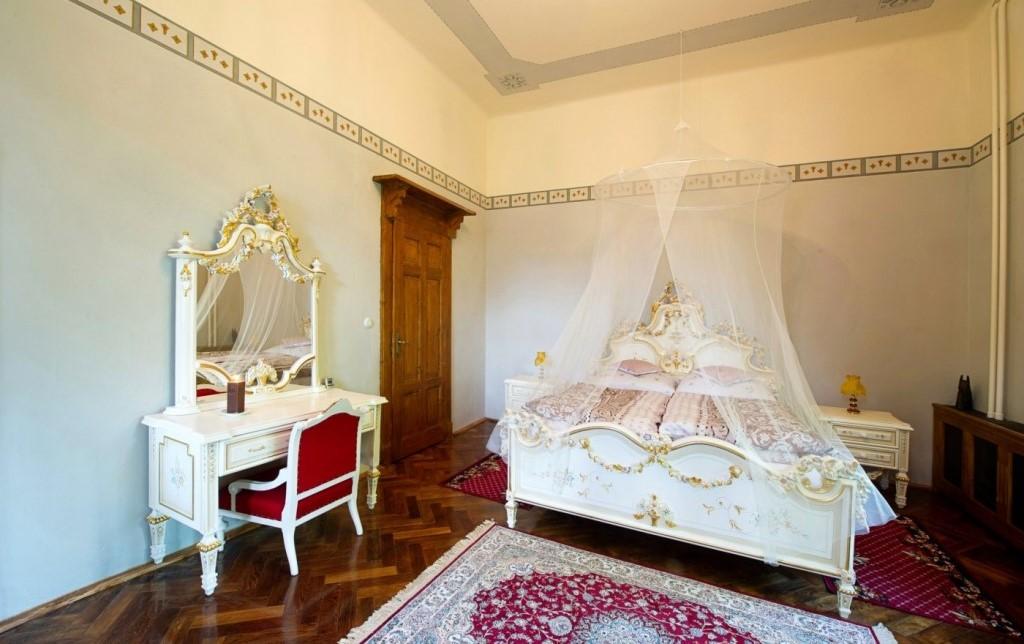Luxusní apartmán Adina Mandlová s dvěma balkony s výhledem na upravovaný park s fontánou a sochami a na jezírko s vodotryskem.