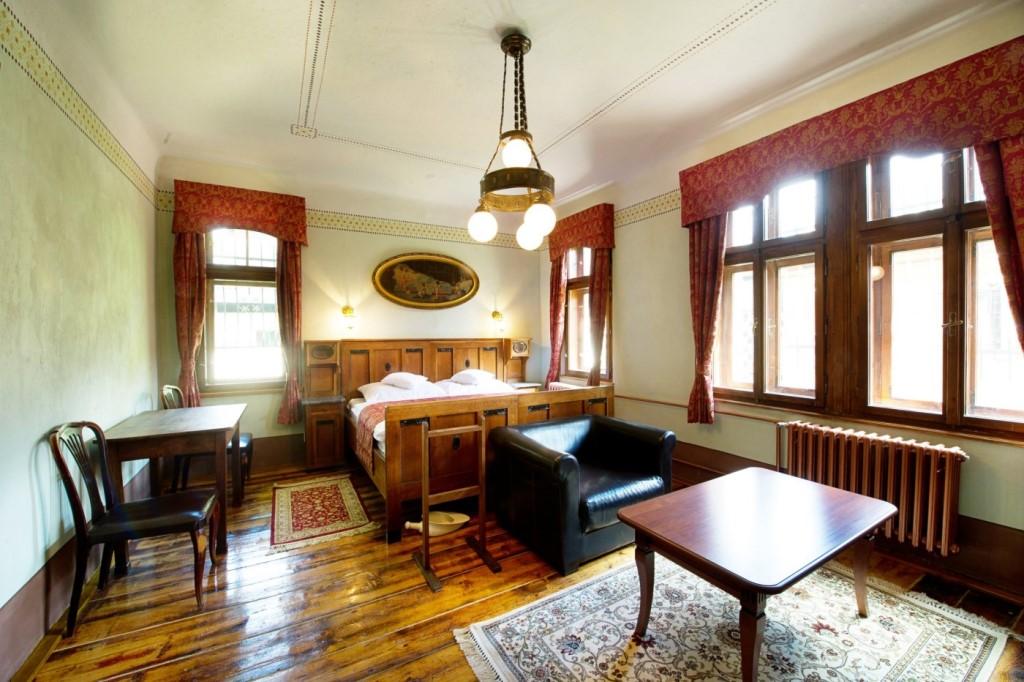Pokoj Vlasta Burian - prostorný pokoj s dřevěným nábytkem zdobeným kovovými prvky stojícím na původní dřevěné podlaze.