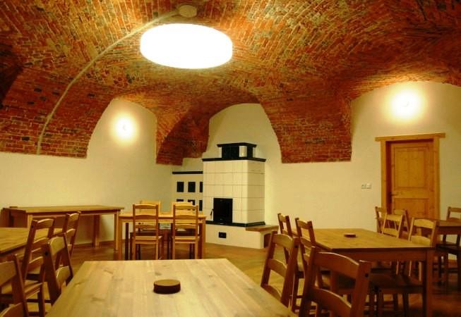 Dominantou v přízemí je velká klenutá společenská místnost s kachlovými kamny.